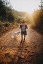 Rear view of father carrying daughter on shoulders while walking with dog on dirt road during sunny day - CAVF59405