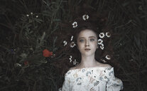 High angle portrait of teenage girl with flowers on hair lying on field - CAVF59408