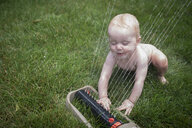 High angle view of naked baby boy playing with sprinkler on grassy field in yard - CAVF59453
