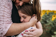 Close-up of mother embracing daughter while standing in sunflower farm - CAVF59495