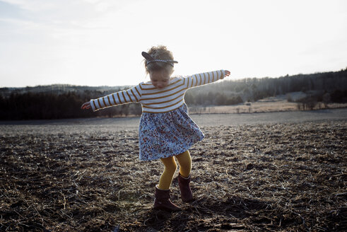 Full length of playful girl with arms outstretched spinning on field - CAVF59522