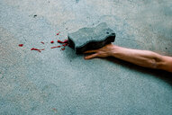 Surreal view of a human hand bleeding under a rock - INGF08986