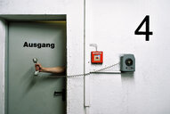 A human hand holding a pay phone with text on a wall - INGF09019