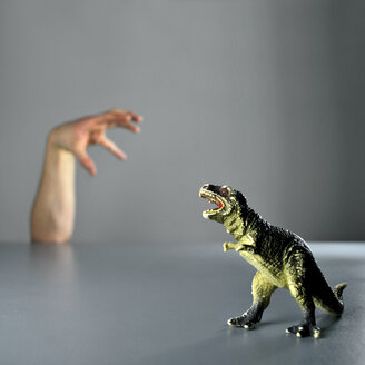 Close-up studio shot of a hand with a toy dinosaur against a grey background - INGF09034