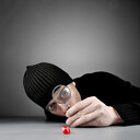 Studio shot of a man with a magnifying glass on a grey background - INGF09040