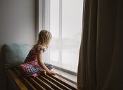 Side view of girl looking through window while sitting at home - CAVF59592