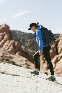 Side view of female hiker with backpack walking on mountain during sunny day - CAVF59637