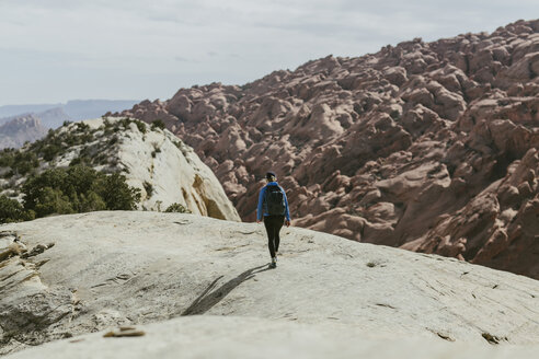 Rear view of hiker with backpack walking on rock during sunny day - CAVF59640