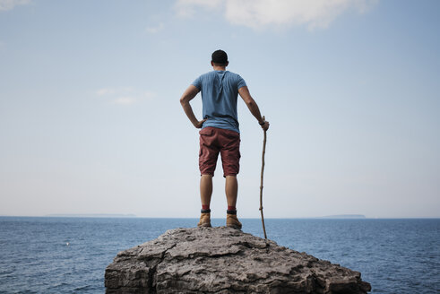 Rear view of hiker with hand on hip holding stick while standing on rock against sea and sky at Bruce Peninsula National Park - CAVF59652