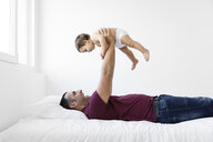 Cheerful father lifting shirtless daughter against wall at home - CAVF59661