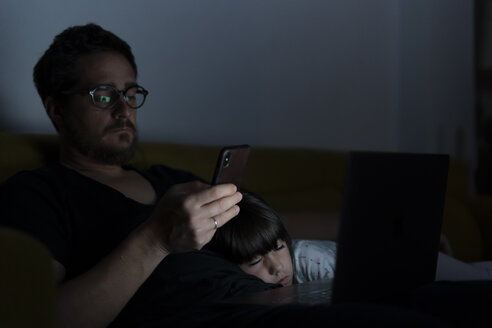 Father using laptop and cell phone on couch at night with daughter sleeping - ERRF00304