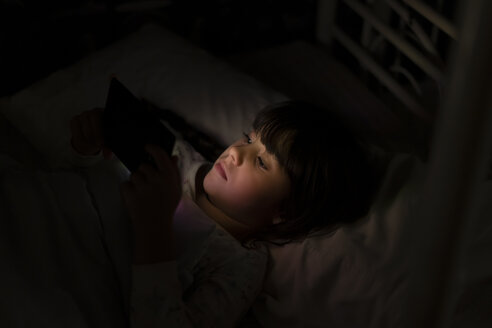 Girl lying in bed using smartphone at night - ERRF00310