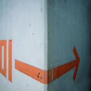 Close-up illustration of an arrow sign on a white wall - INGF09274