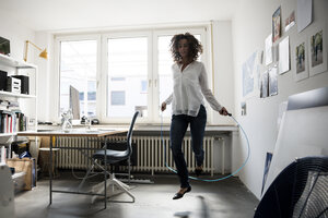 Businesswoman in office, training with skipping rope - MOEF01889