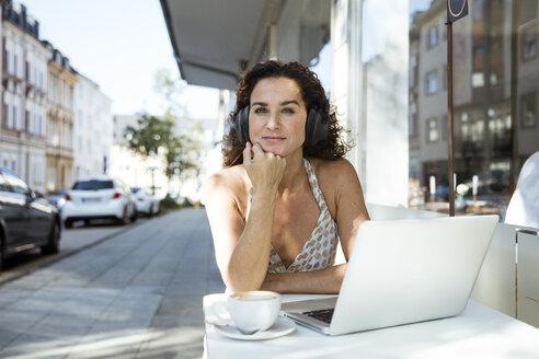 Mature woman sitzting in cafe, wearing headphones, using laptop - MOEF01895