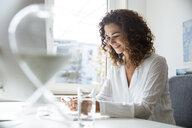Businesswoman using smartphone in office - MOEF01910