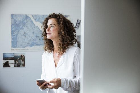 Businesswoman using smartphone in office - MOEF01913