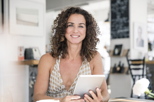 Mature woman sitting in coffee shop, using digital tablet - MOEF01925