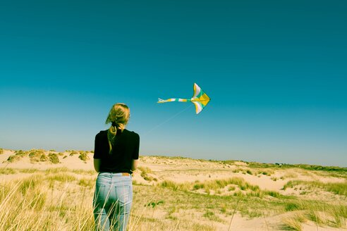 Woman playing with a kite on the beach. Rear view - INGF09328