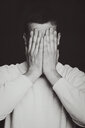 Black and white shot of a man covering his face with his hands - INGF09358