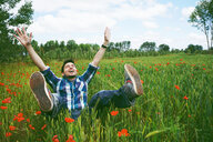 A happy young man with his arms raised in a field - INGF09364