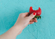 A person holding a half eaten strawberry - INGF09409
