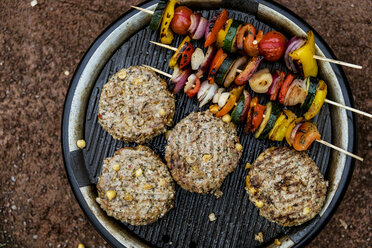 Food on a barbeque, vegetable kebabs and home made burgers, cooking outdoors. - MINF09718