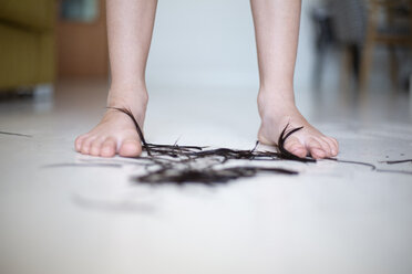 Girl standing barefoot on floor with cut heir, close-up - ERRF00314