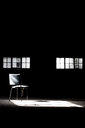 Light streaming through windows on an empty chair in a deserted building - INGF09610