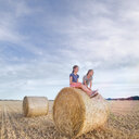 Full length of young couple sitting on hay bales in field. - INGF09658
