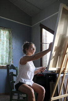 Young woman painting in her atelier - ERRF00329