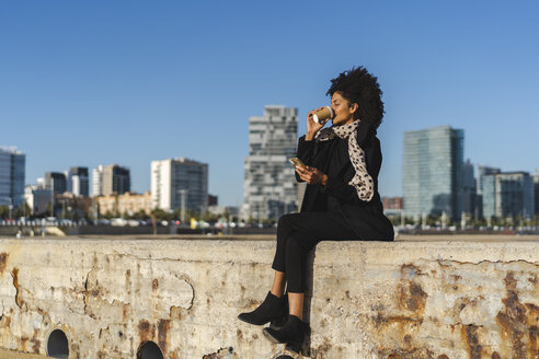 Spain, Barcelona, woman with smartphone sitting on a wall drinking coffee to go - AFVF02069