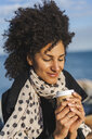 Portrait of smiling woman enjoying coffee to go near the sea - AFVF02072