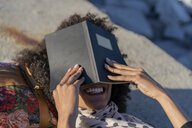 Laughing woman lying on a wall hiding her face behind a notebook - AFVF02087
