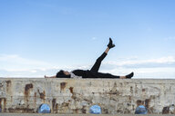 Woman dressed in black relaxing on a wall - AFVF02090