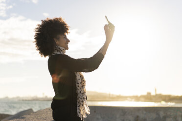 Smiling woman taking selfie with smartphone near the sea - AFVF02096