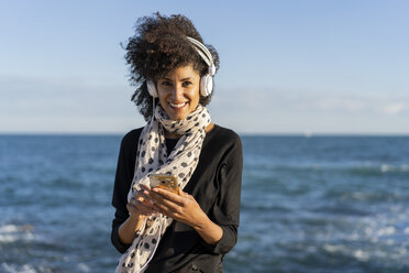 Portrait of smiling woman listening music with smartphone and headphones in front of the sea - AFVF02102