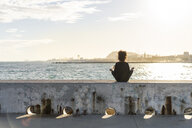 Spain, Barcelona, back view of  woman sitting on wall in front of the sea meditating - AFVF02105