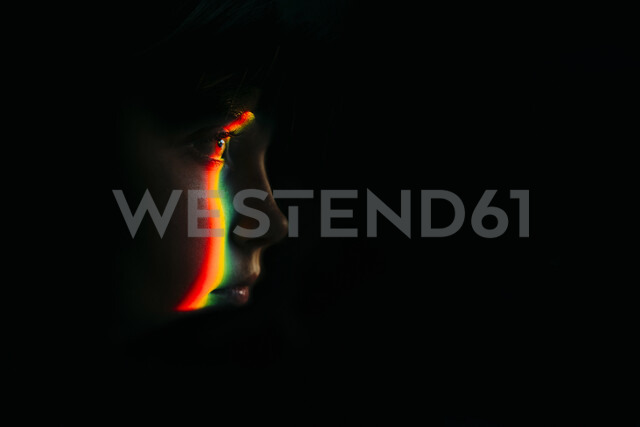 Close-up of spectrum on girl in darkroom - CAVF59676 - Cavan Images/Westend61
