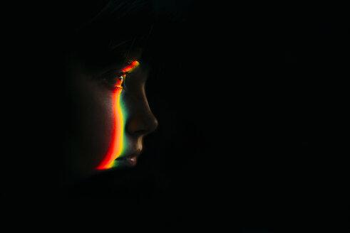 Close-up of spectrum on girl in darkroom - CAVF59676