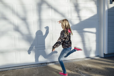 Full length of girl dancing on footpath against wall - CAVF59685