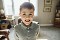 Portrait of smiling boy standing against window at home - CAVF59703