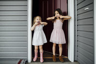 Full length of girls sticking out tongues while standing at doorway - CAVF59715