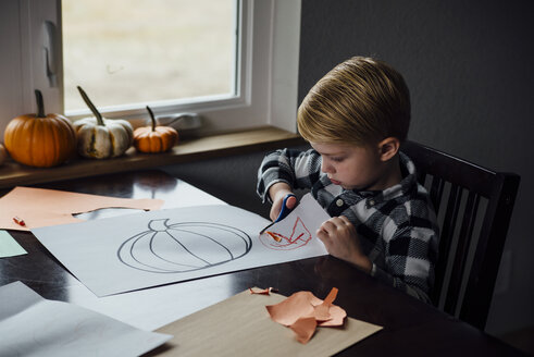 High angle view of boy cutting paper with pumpkin drawing on it at home during Halloween - CAVF59733
