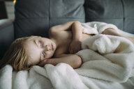 Shirtless boy sleeping on sofa at home - CAVF59784