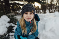 Portrait of girl sitting on snow field - CAVF59787