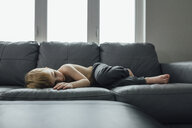Full length of shirtless boy lying on sofa at home - CAVF59796