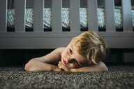 Thoughtful boy lying on rug under bed at home - CAVF59811
