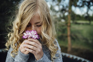 Close-up of girl smelling flower - CAVF59823