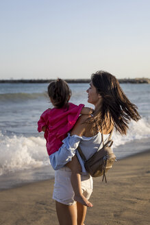 Mother and daughter standing on the beach at sunset - MAUF01901